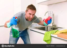 young man holding cleaning detergent spray and sponge washing home