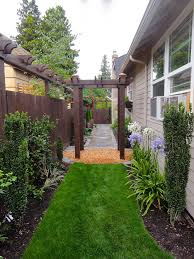 narrow side yard with arbor diagonal pavers planters and large