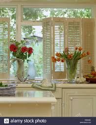 Kitchen Windowsill Red Gerberas And Orange Striped Tulips In Glass Vases On Kitchen
