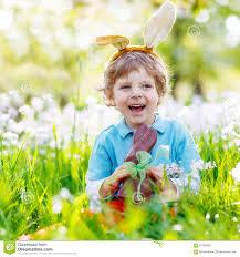 little kid boy eating chocolate easter bunny stock photo image