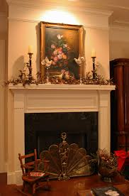 christmas fireplace with candles and painting above amys office