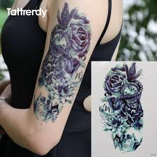 black ink pirate skull with flowers tattoo on women left half sleeve