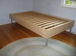 simple wooden ikea twin size bed frame with metal legs on braided