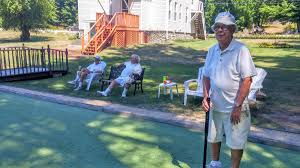 this backyard croquet court in rye attracts professionals and