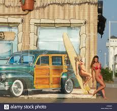 woman in red bikini mimics woman in wall mural corner 24 surf shop stock photo woman in red bikini mimics woman in wall mural corner 24 surf shop virginia beach va