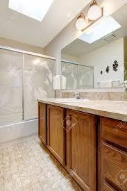 bathroom vanity cabinet with glass door shower and skylight