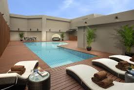 elegant modern pool design in the backyard with green plants