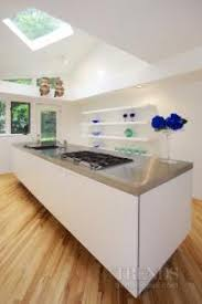 floating island kitchen island in minimalist white kitchen with concealed appliances open