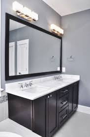 bathroom grey wall and dark cabinet with bathroom light fixtures