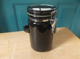 black pottery kitchen canister with silver hinge and built in