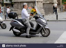 peugeot england scooter rider carrying bunches of flowers in central thessaloniki