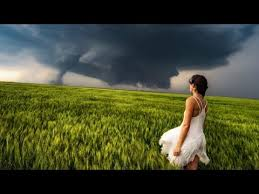 fearless storm chaser wearing a dress strikes a pose in front of