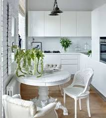 white kitchen with modern cabinets and white pedestal table also