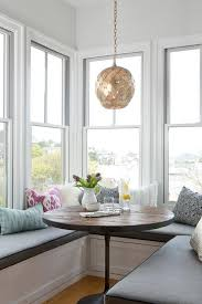 u shaped window seat with accent pillows and round wood table in
