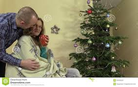 careful husband give wife cup of coffee tea near christmas tree