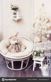 plush rabbit sitting in a circle chair near the white christmas