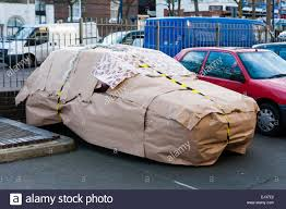 car wrapped in wrapping paper car in car park wrapped up as secret santa christmas