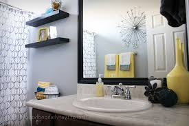 gray and yellow bathroom towels floating natural wood cabinets