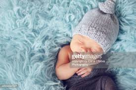 newborn baby boy sleeping peacefully wearing knit hat stock photo