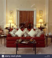 cream cushions on red velour sofa in front of lighted lamps in