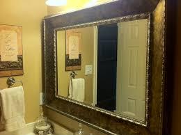 renewing bathroom décor by installing framed bathroom mirrors