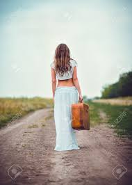 with suitcase in going away by a field road stock