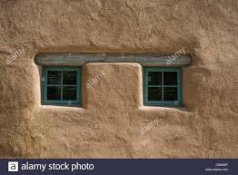 pair of small square windows under wooden beam in old adobe style