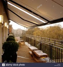Large Awning Box Hedge And Wooden Bench On Penthouse Balcony With Railing And