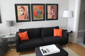 simple but elegant living room black couch nice art orange