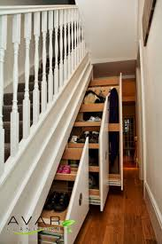 under stairs shelving with black staircase and bookshelves