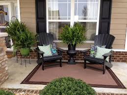 front porch decorated with adirondack chairs and potted plants