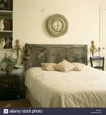 circular distressed wooden clock above bed with reclaimed carved