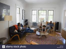 Family Relaxing And Using Technology In Living Room Stock Photo - Family in living room