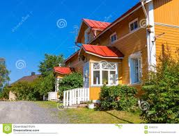 wooden yellow house with red roof in scandinavian style stock