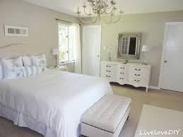 cream wooden bed with white bed sheet plus gray bench and white