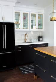 black refrigerator with black base cabinets and white upper