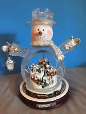 kinkade inside a sledding snowman snowglobe by the