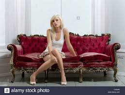 blonde in white clothes and heels sitting on red velvet sofa