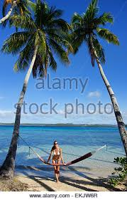 woman in hammock and palm trees at sunset coral coast viti levu