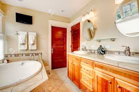 light tones bathroom with wood cabinets tile floor tv and