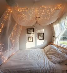 white hanging canopy bed curtains with string twinkle lights over