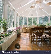 terracotta floor tiles and wooden furniture in conservatory dining