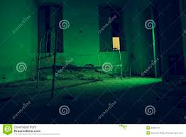 light halloween background light painted in green abandoned bed in dark room stock photo