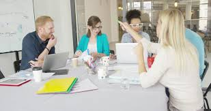 3 adults working in casual startup office focus on