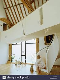 woman sitting on staircase with dog in hall in modern country barn