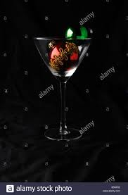 cocktail glass and two christmas baubles black background red