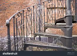 black metal spiral staircase near brick stock photo 1203978