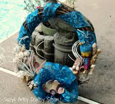 decorating charming seashell wreath with blue ribbon for wall