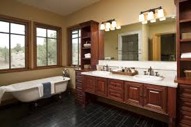 admiring bathroom design is demonstrated by terrific big tiles cozy bathroom design with black tile floor also brown paint wall and wall lighting above rectangular