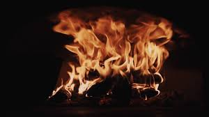 blazung red fire flames burning logs in dark room fireplace close